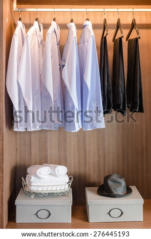 shirts and pants hanging  on rack in wooden wardrobe with boxes on shelf - stock photo
