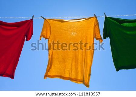 Shirts on clothesline against blue sky. - stock photo