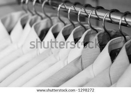 Shirts on hangers at the show, shallow DOF, b&w version - stock photo