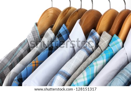 Shirts with ties on wooden hangers isolated on white - stock photo