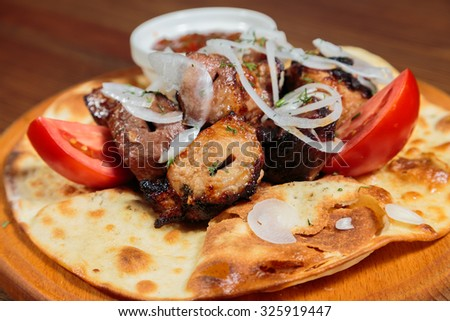 Shish kebab on pita bread with tomatoes and onions. - stock photo