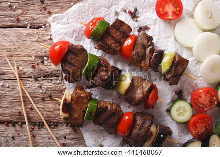 Shish kebab on skewers with vegetables close-up on the table. horizontal view from above - stock photo