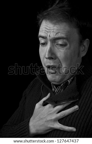 shock, heart attack. man with hand on chest black and white with copy space - stock photo