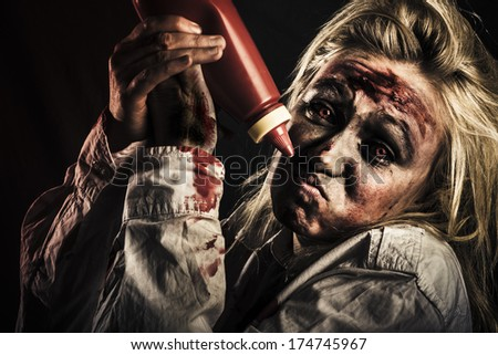 Shock horror food concept with a scary zombie woman out of tomato sauce at halloween party - stock photo