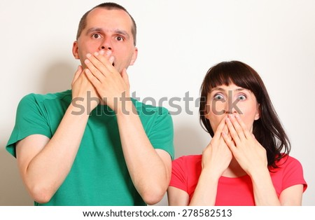 Shocked and surprised woman and man, hands covering mouth, big eyes, face expression and human emotion - stock photo