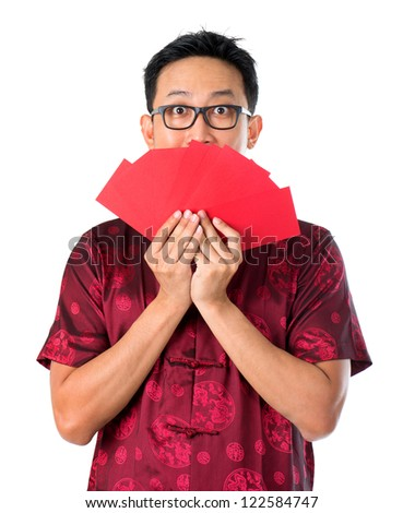 Shocked Asian Chinese man holding many red packets / ang pow  for happy chinese new year, isolated over white background - stock photo