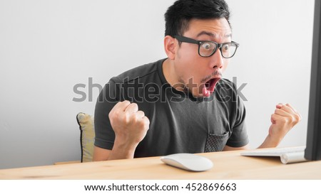 Shocked Asian man with his work. Graphic designer get good income. - stock photo