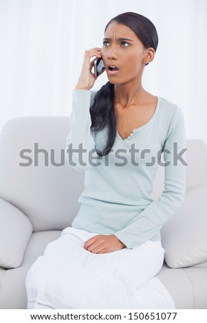 Shocked attractive woman sitting on cosy sofa in bright living room having a phone call - stock photo