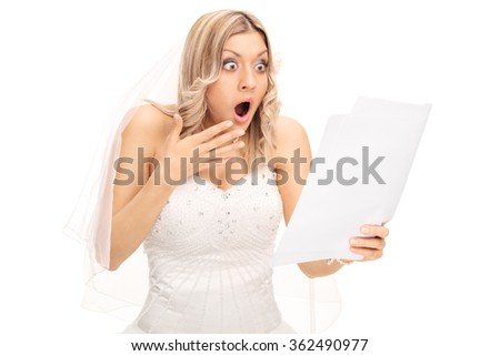 Shocked blond bride looking at a piece of paper in disbelief isolated on white background - stock photo