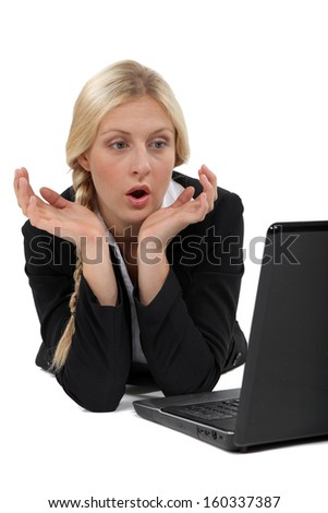 Shocked blond businesswoman sat in front of laptop - stock photo