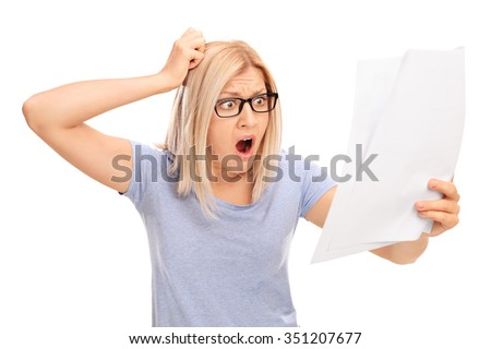Shocked blond woman looking at a piece of paper in disbelief isolated on white background - stock photo