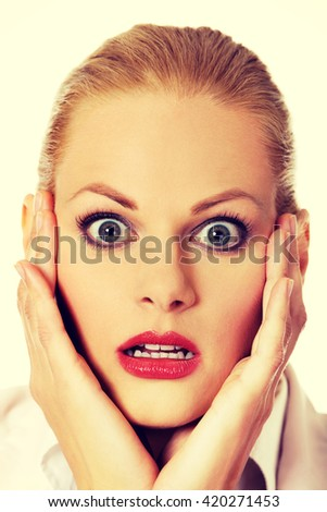 Shocked business woman holding hands on chin - stock photo