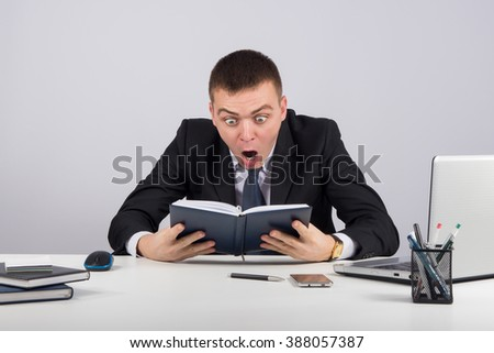 Shocked businessman in panic  on gray background - stock photo