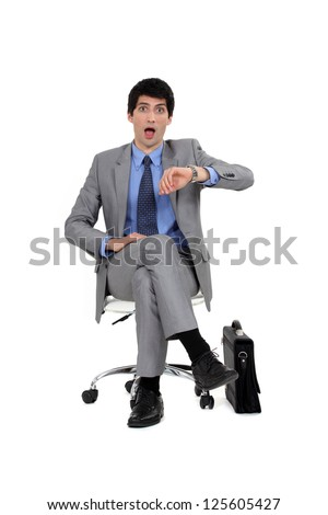 Shocked businessman looking at the time - stock photo