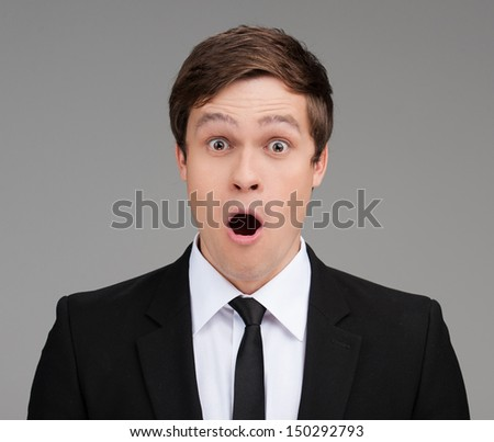 Shocked businessman. Portrait of surprised young businessman looking at camera and keeping his mouth open while isolated on grey - stock photo