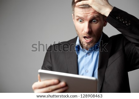 Shocked businessman with digital tablet - stock photo