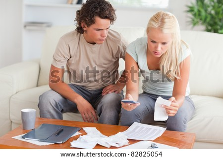 Shocked couple calculating their expenses in the living room - stock photo