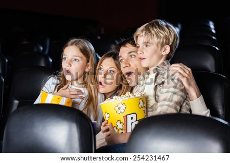 Shocked family of four with popcorn watching movie in cinema theater - stock photo
