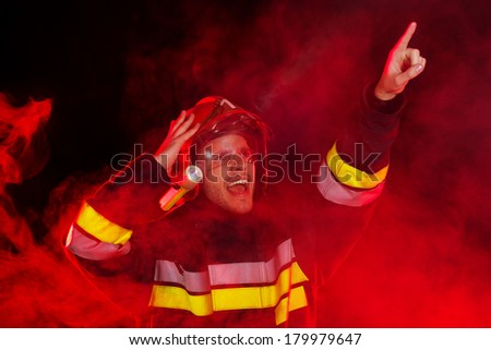 Shocked firefighter in action. Shouting fireman in smoke holding hand on helmet and pointing up. Head and shoulders studio shot on black background. - stock photo