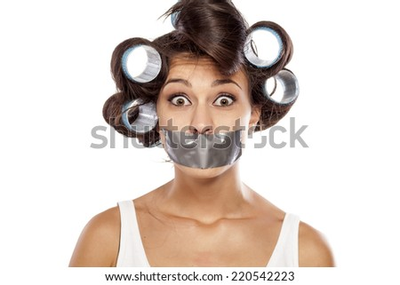 shocked housewife with curlers and adhesive tape over her mouth - stock photo