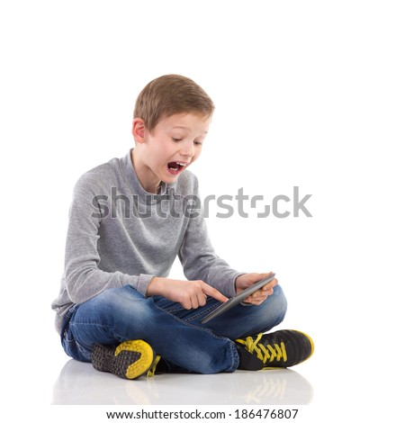 Shocked kid with tablet. Shouting young boy sitting on the floor with legs crossed, using tablet. Full length studio shot isolated on white. - stock photo