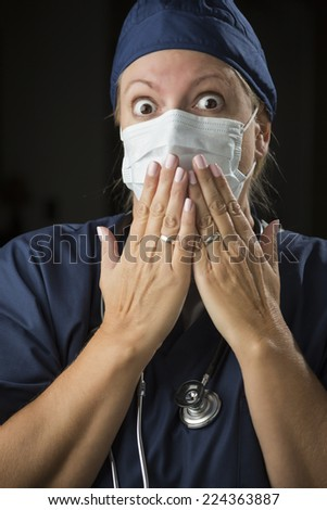Shocked Looking Female Doctor or Nurse with Hands in Front of Mouth. - stock photo