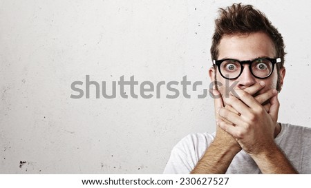 Shocked man covering his mouth with hands - stock photo