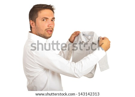 Shocked man holding shrunk shirt and looking at camera isolated on white background - stock photo