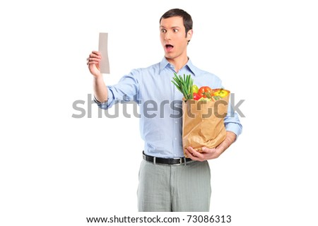Shocked man looking at store receipt and holding a grocery bag isolated on white background - stock photo