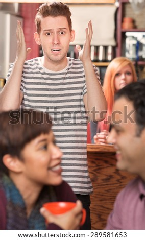 Shocked man with lip ring watching cheating partner in cafe - stock photo