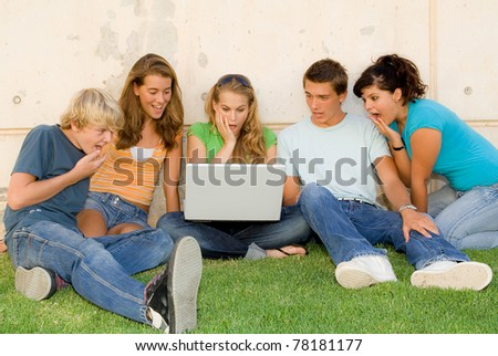 shocked or surprised teens with laptop computer or notebook - stock photo