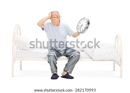Shocked senior man in pajamas sitting on a bed and holding a big wall clock isolated on white background - stock photo
