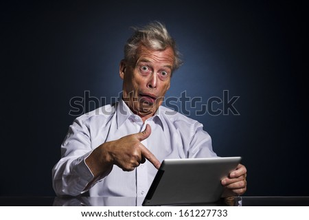 Shocked senior man pointing to his tablet computer with his finger with a look of appalled disbelief and confusion, humorous upper body studio portrait - stock photo