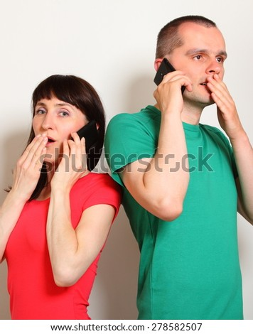 Shocked woman and man receive an unexpected message while talking on mobile phone, hands covering mouth, face expression and human emotion - stock photo