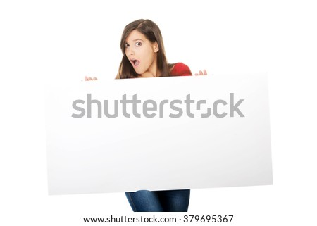 Shocked woman holding empty banner. - stock photo