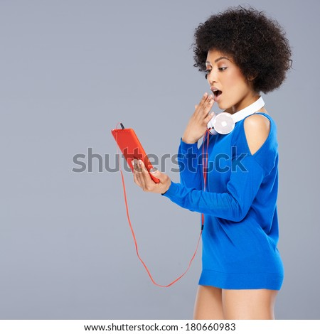 Shocked woman looking at her music storage device with her hand raised to her open mouth as she views something on the screen with the earphones dangling round her neck - stock photo