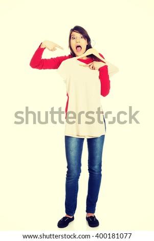 Shocked woman pointing at new shirt. - stock photo