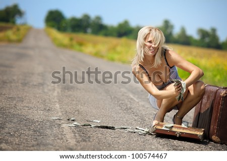 Shocked woman throwing dollars into air on countryside road - stock photo