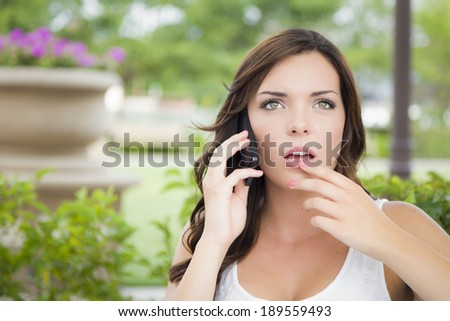 Shocked Young Adult Female Talking on Cell Phone Outdoors on Bench. - stock photo