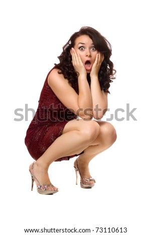Shocked young brunette in red dress. Isolated - stock photo