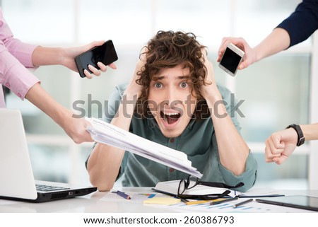 Shocked young businessman looking at camera. Hands with gadgets around him. Office interior with window. Concept for overworking - stock photo