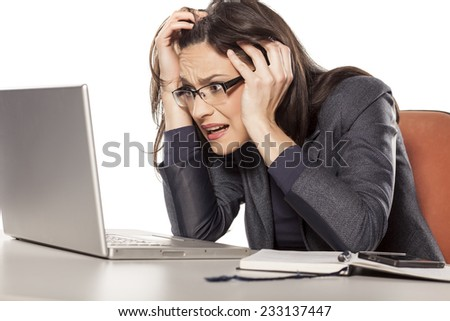 shocked young businesswoman looking in her laptop - stock photo