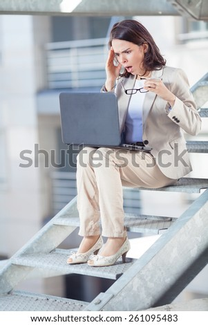 Shocked young businesswoman working on laptop - stock photo