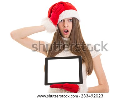 Shocked young Christmas woman with digital tablet. Closeup studio shot of teenage girl showing tablet with blank isolated screen. Copy space. - stock photo