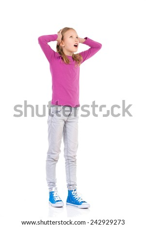 Shocked young girl young holding head and looking up. Full length studio shot isolated on white. - stock photo
