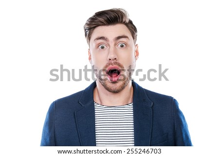 Shocking news. Portrait of shocked young man looking at camera and keeping mouth open while standing against white background - stock photo