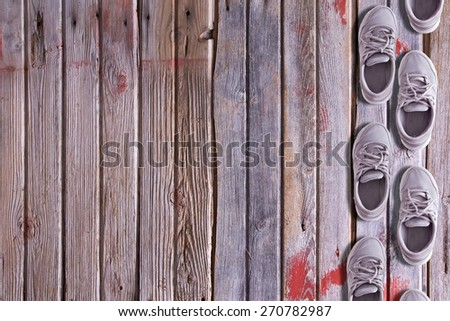 Shoe border with a double row of worn trainers or sneakers arranged as though walking on a textured hardwood background of old floorboards with wood grain, red paint remnants and copy space - stock photo