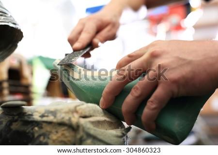shoe factory.Shoemaker sews shoes - stock photo
