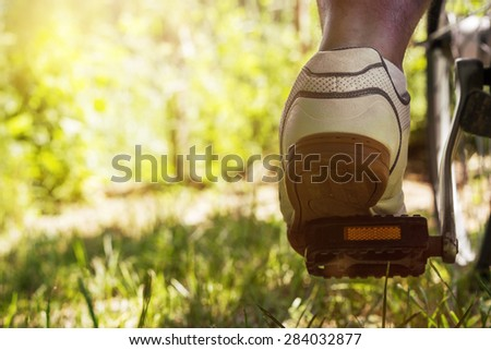 shoe on the bike pedal in front of bloomy green nature background - stock photo