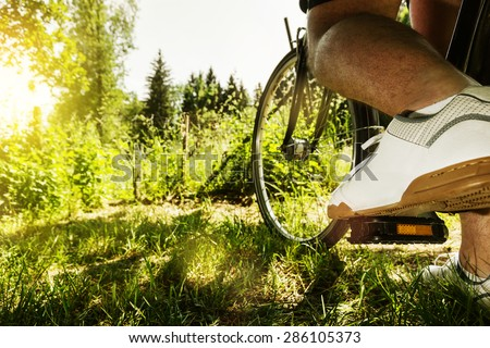 shoe on the bike pedal in front of bloomy sunny nature background - stock photo
